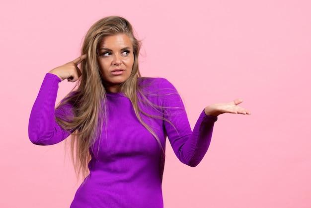Vooraanzicht van een jonge vrouw die zich voordeed in een mooie paarse jurk op de roze muur