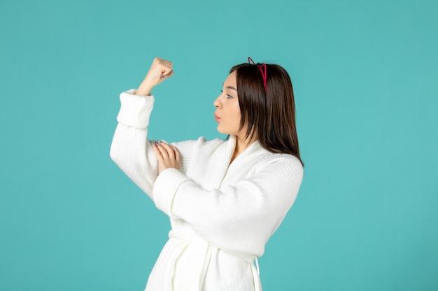 Vooraanzicht van een jonge vrouw in een badjas die haar sterke arm op een blauwe muur laat zien