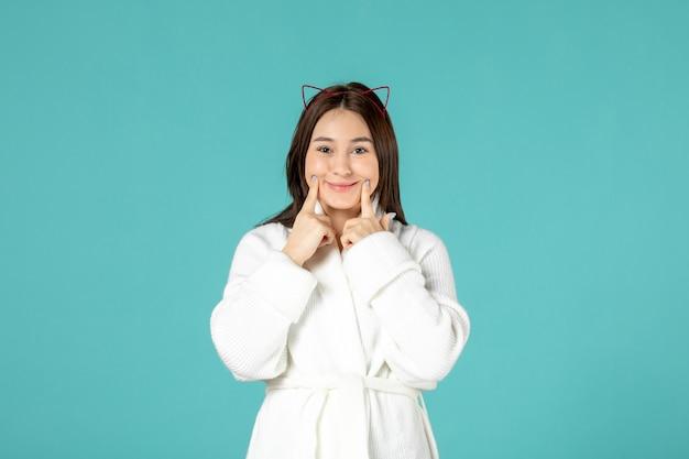 Vooraanzicht van een jonge vrouw in een badjas die lacht op een blauwe muur