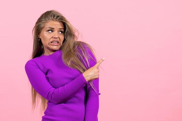 Vooraanzicht van een jonge vrouw in een mooie paarse jurk die zich voordeed op de roze muur