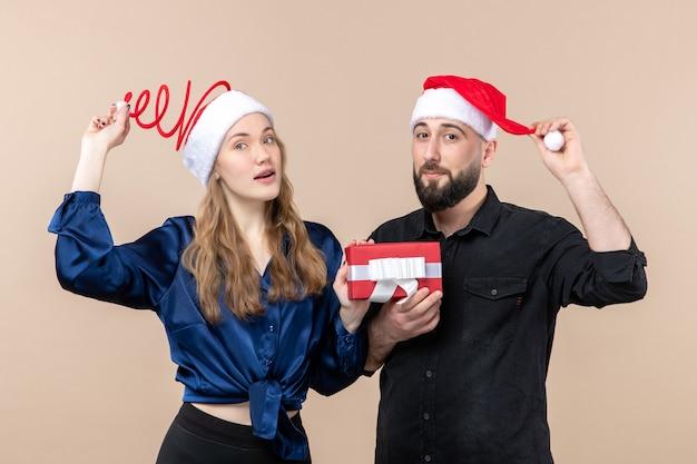 Vooraanzicht van een jonge vrouw met een man die allebei zijn cadeau aan haar vasthoudt op de roze muur