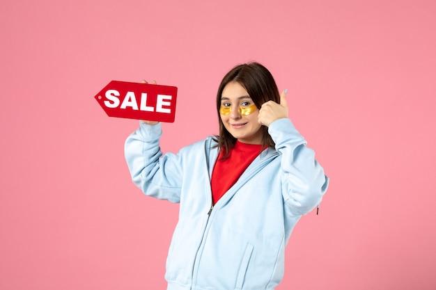 Vooraanzicht van een jonge vrouw met ooglapjes die een verkoopbanner vasthoudt en lacht op een roze muur