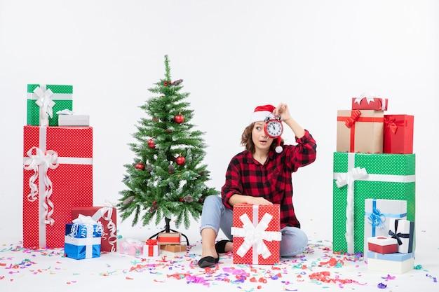 Vooraanzicht van een jonge vrouw rond kerstcadeautjes zitten met klokken op de witte muur