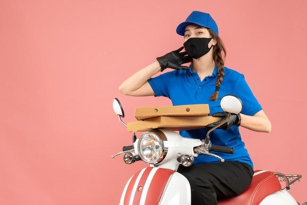 Vooraanzicht van een jonge vrouwelijke koerier met een medisch masker en handschoenen die op een scooter zit en bestellingen aflevert op een pastelkleurige perzikachtergrond