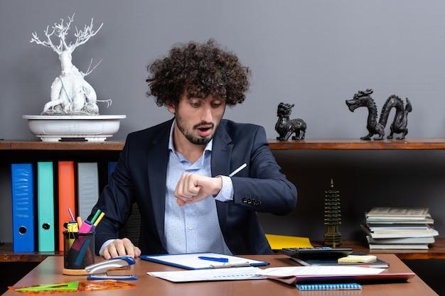 Vooraanzicht van een jonge zakenman die aan het bureau zit en de tijd controleert