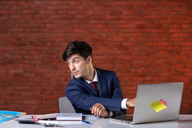 Vooraanzicht van een jonge zakenman die achter zijn werkplek zit in pak met behulp van laptop werkplan aannemersbezetting zakelijk project zakelijke baanbouwers
