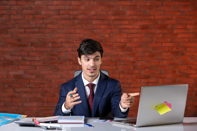 Vooraanzicht van een jonge zakenman die achter zijn werkplek zit met een laptop in pak werkplan aannemersbezetting zakelijk project zakelijke baanbouwers