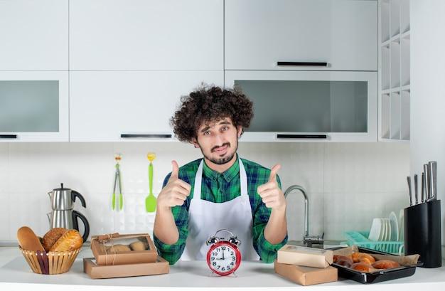 Vooraanzicht van een jonge zelfverzekerde man die achter de tafelklok staat en verschillende gebakjes erop die een goed gebaar maken in de witte keuken