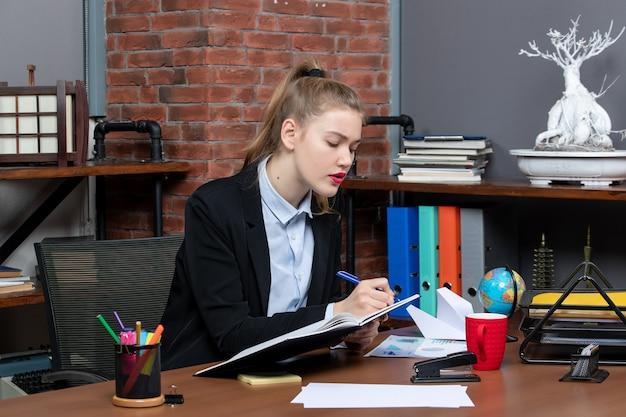 Vooraanzicht van een jonge zelfverzekerde vrouwelijke assistent die aan haar bureau zit en een document op kantoor vasthoudt