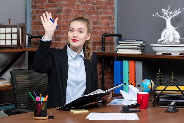 Vooraanzicht van een jonge zelfverzekerde vrouwelijke assistent die aan haar bureau zit en een document vasthoudt dat hallo zegt tegen iemand op kantoor