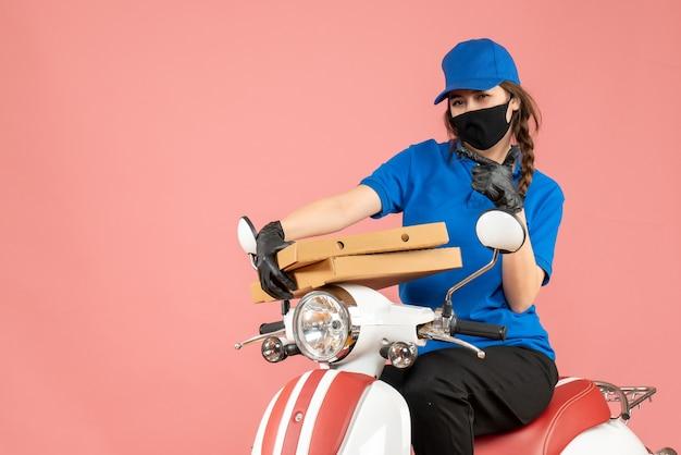 Vooraanzicht van een jonge zelfverzekerde vrouwelijke koerier met een medisch masker en handschoenen die op een scooter zitten en bestellingen afleveren op een pastelkleurige perzikachtergrond