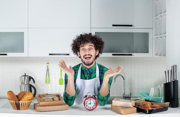 Vooraanzicht van een jonge zich afvragende man die achter de tafelklok staat, verschillende gebakjes erop in de witte keuken