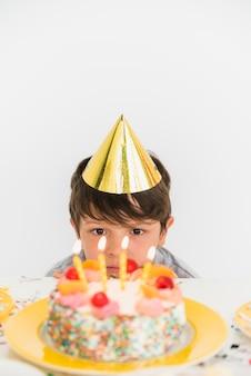 Vooraanzicht van een jongen die verjaardagscake en verlichte kaarsen bekijkt