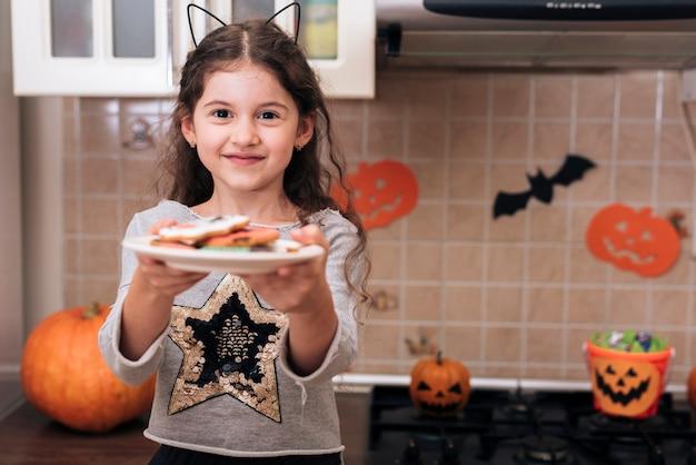 Vooraanzicht van een klein meisje met een bord koekjes