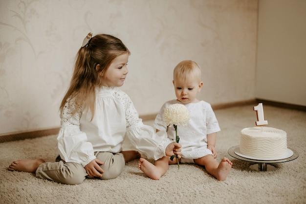 Vooraanzicht van een klein schattig meisje dat haar jongere zusje een bloem geeft voor haar eerste verjaardag