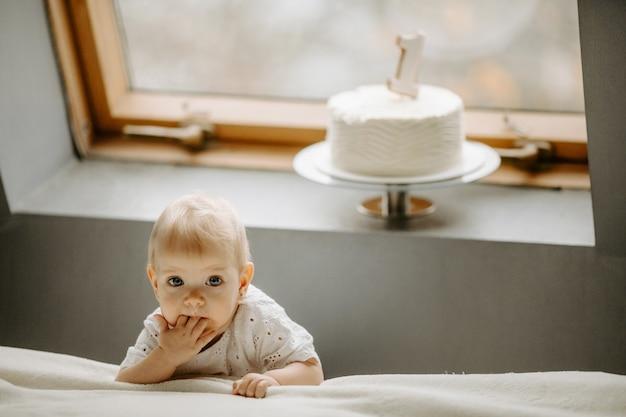 Vooraanzicht van een klein vrouwelijk kind dat bij een raam staat
