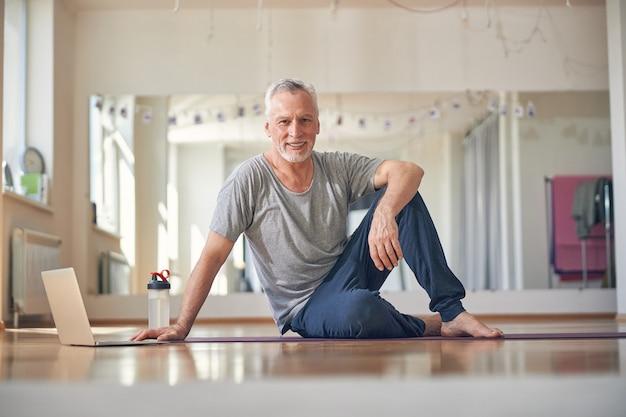 Vooraanzicht van een knappe fitte man op de yogamat die voor de camera poseert