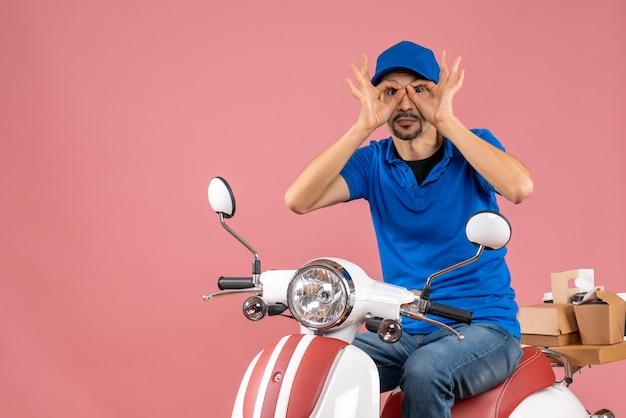 Vooraanzicht van een koeriersman met een hoed die op een scooter zit en een brilgebaar maakt met beide kanten op een pastelkleurige perzikachtergrond