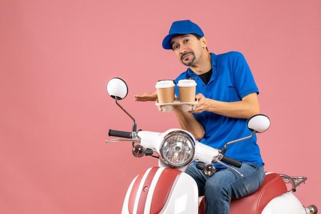 Vooraanzicht van een koeriersman met een hoed die op een scooter zit en precies iets maakt op een pastelkleurige perzikachtergrond