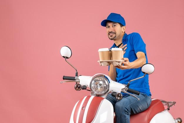 Vooraanzicht van een koeriersman met een hoed die op een scooter zit en zich trots voelt op een pastelkleurige perzikachtergrond