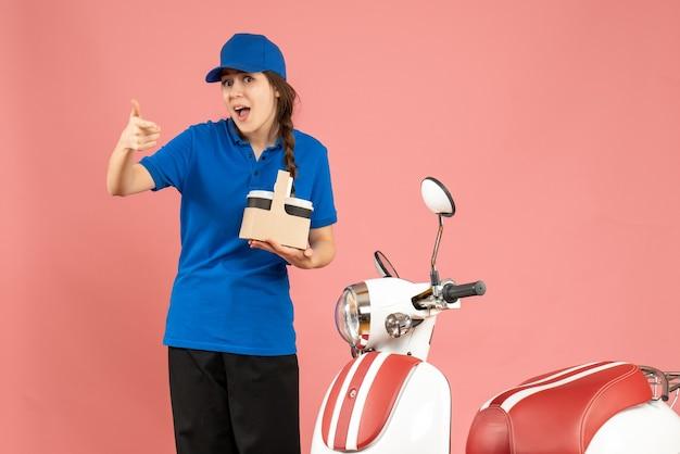 Vooraanzicht van een koeriersmeisje dat naast een motorfiets staat die koffie vasthoudt en een goed gebaar maakt op een pastelkleurige perzikkleurige achtergrond