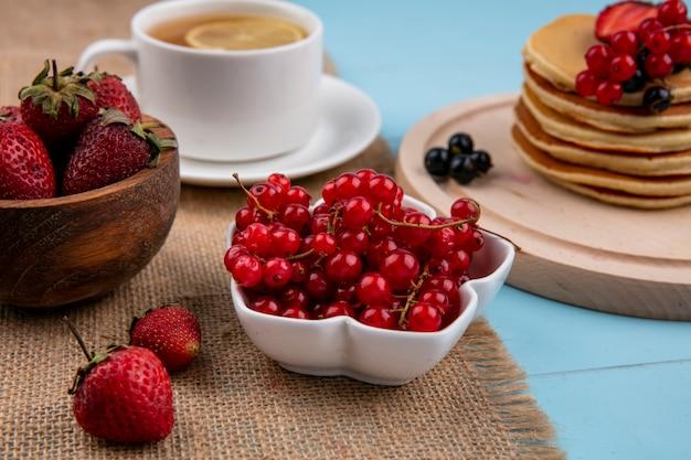 Vooraanzicht van een kopje thee met een schijfje citroen en pannenkoeken met rode en zwarte bessen en aardbeien op een blauwe ondergrond