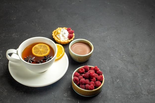 Vooraanzicht van een kopje zwarte thee met citroen geserveerd met chocolade framboos op donkere achtergrond