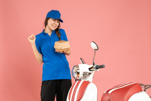 Vooraanzicht van een lachend, gelukkig, emotioneel koeriersmeisje dat naast een motorfiets staat met cake op een pastelkleurige perzikkleurige achtergrond