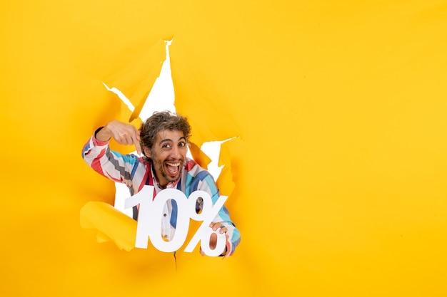 Vooraanzicht van een lachende jongeman die tien procent wijst in een gescheurd gat in geel papier