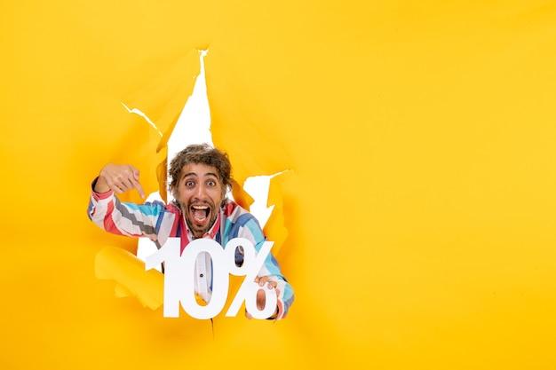 Vooraanzicht van een lachende jongeman die tien procent wijst in een gescheurd gat in geel papier Gratis Foto