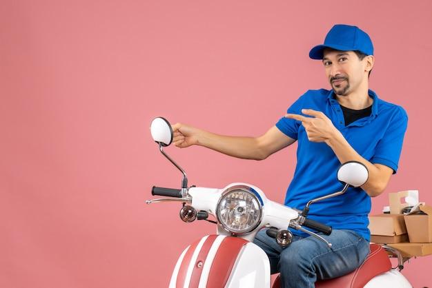 Vooraanzicht van een lachende koeriersman met een hoed die op een scooter zit en iets wijst op een pastelkleurige perzikachtergrond