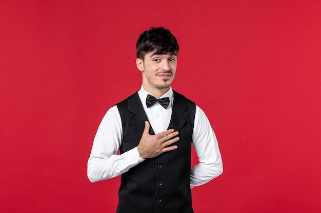 Vooraanzicht van een lachende mannelijke ober in een uniform met vlinderdas om de nek en bedankt aan iemand op de rode muur