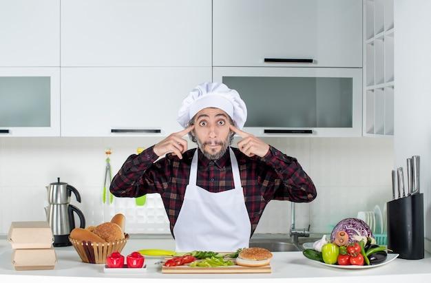 Vooraanzicht van een man met grote ogen die vingers op zijn slaap legt in de keuken