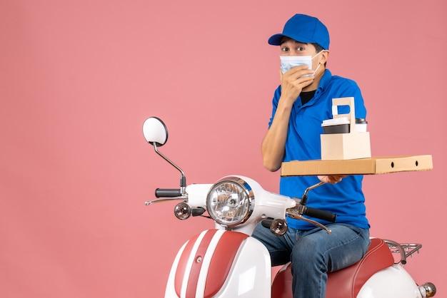 Vooraanzicht van een mannelijke bezorger met een masker met een hoed op een scooter met bestellingen op een pastelkleurige perzikachtergrond peach