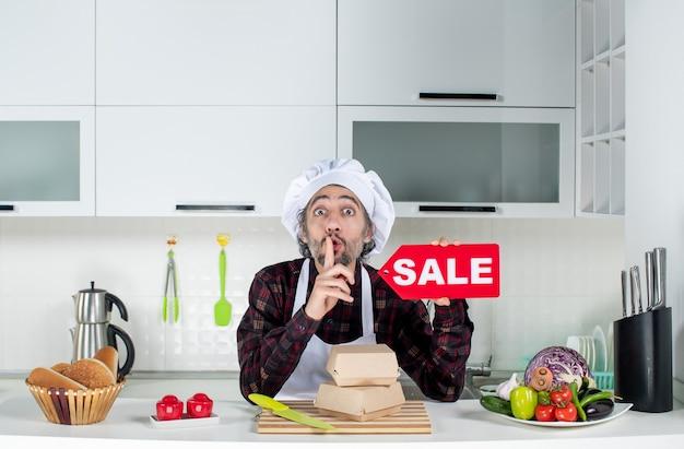 Vooraanzicht van een mannelijke chef-kok in uniform die een rood verkoopbord omhoog houdt en een stil teken maakt in de moderne keuken