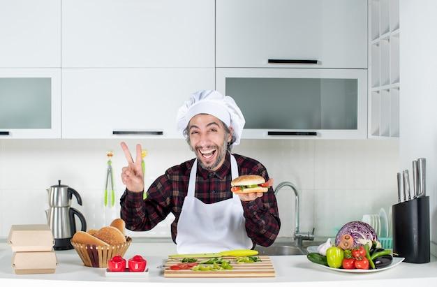 Vooraanzicht van een mannelijke kok die een overwinningsteken maakt terwijl hij een hamburger omhoog houdt die achter de keukentafel staat