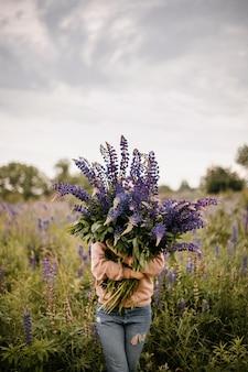 Vooraanzicht van een meisje dat zich verschuilt achter een enorm boeket wilde violette lupines op een groen veld op een bewolkte zomerdag