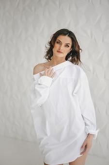 Vooraanzicht van een mooie brunette vrouw gekleed in een wit overhemd van de man, staande op een witte achtergrond