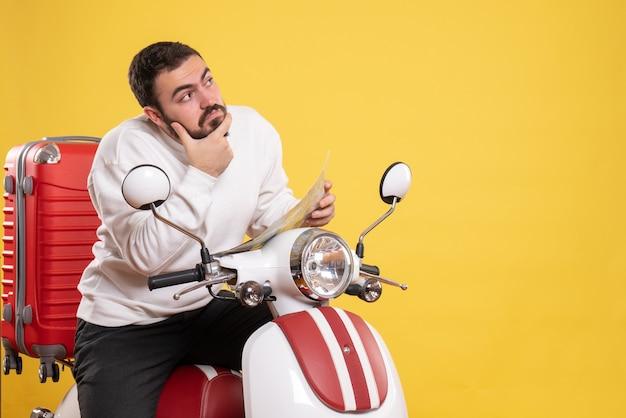Vooraanzicht van een nadenkende jongeman die op een motorfiets zit met een koffer erop met een kaart op een geïsoleerde gele achtergrond