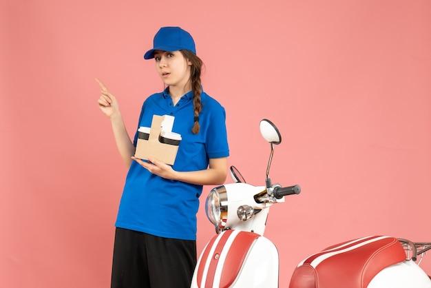Vooraanzicht van een nieuwsgierig koeriersmeisje dat naast een motorfiets staat die koffie vasthoudt en omhoog wijst op een pastelkleurige perzikkleurige achtergrond