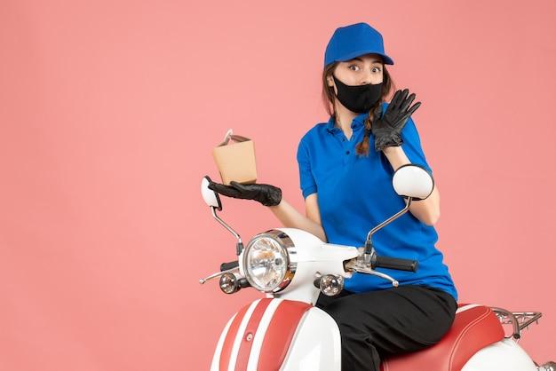 Vooraanzicht van een nieuwsgierige bezorger met een medisch masker en handschoenen die op een scooter zit en bestellingen aflevert op een pastelkleurige perzikachtergrond