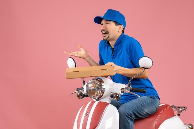 Vooraanzicht van een nieuwsgierige koeriersman met een hoed die op een scooter zit en de bestelling vasthoudt op een pastelkleurige perzikachtergrond