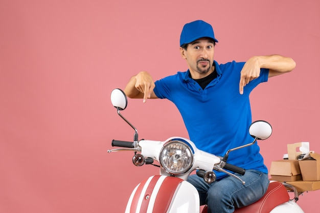 Vooraanzicht van een nieuwsgierige koeriersman met een hoed die op een scooter zit en naar beneden wijst op een pastelkleurige perzikachtergrond