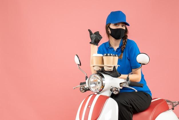 Vooraanzicht van een nieuwsgierige vrouwelijke bezorger met een medisch masker en handschoenen die op een scooter zit en bestellingen vasthoudt die op een pastelkleurige perzikachtergrond wijzen