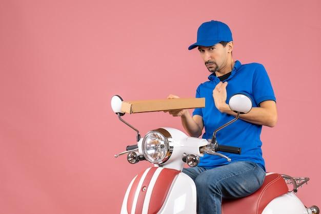 Vooraanzicht van een onzekere koeriersman met een hoed die op een scooter zit en de bestelling vasthoudt op een pastelkleurige perzikachtergrond