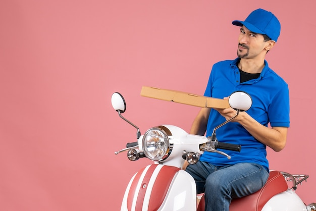 Vooraanzicht van een onzekere, onzekere koeriersman met een hoed die op een scooter zit en de bestelling vasthoudt op een pastelkleurige perzikachtergrond