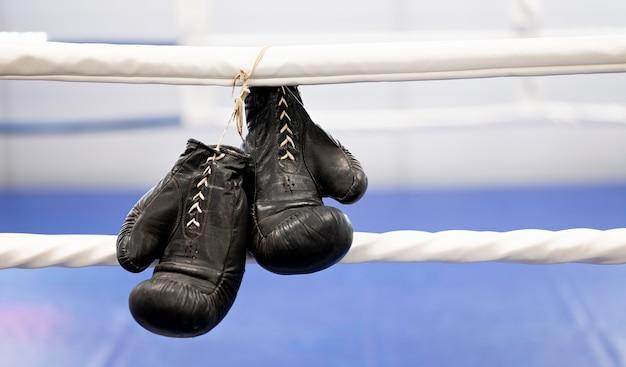 Vooraanzicht van een paar bokshandschoenen naast ring