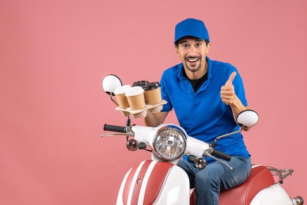 Vooraanzicht van een positieve, gelukkige koeriersman met een hoed die op een scooter zit en een goed gebaar maakt op een pastelkleurige perzikachtergrond