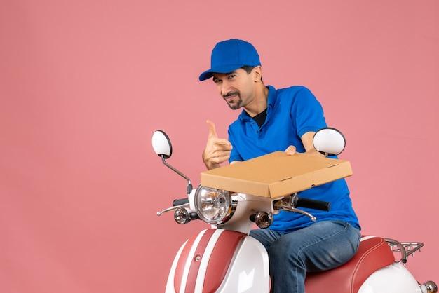 Vooraanzicht van een positieve koeriersman met een hoed die op een scooter zit en de bestelling vasthoudt en een goed gebaar maakt op een pastelkleurige perzikachtergrond