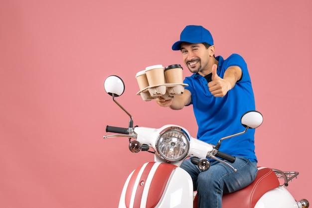 Vooraanzicht van een positieve koeriersman met een hoed die op een scooter zit en een goed gebaar maakt op een pastelkleurige perzikachtergrond